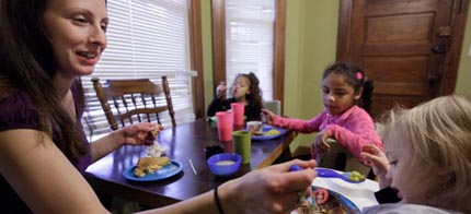 A mother serves lunch to her three children. She is a single mother and full-time student, and food stamps often don't cover the food her family needs each month. (photo: M. Spencer Green/AP)