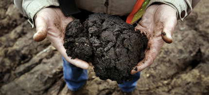 A worker holds a glob of tar sands from a mine in Alberta, Canada. (photo: Lara Solt/Corbis)