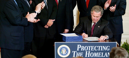 President George W. Bush signs the Homeland Security Act of 2002, 11/25/02. (photo: Stephen Jaffe/Getty Images)