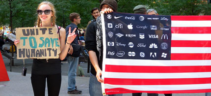 Occupy Wall Street demonstrators hold signs and a flag in front of Liberty Plaza, NYC, where hundreds are staying throughout the day and night in protest of Wall Street's corruption, 09/19/11. (photo: Cate Woodruff/Reader Supported News)
