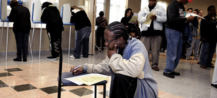 Voter Ira Stafford used a chair to improvise his own voting booth inside a crowded Minneapolis polling place on Election Day. (photo: Bill Alkofer/MPR)