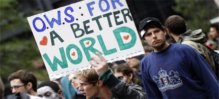 A demonstrator holds a sign during an Occupy Wall Street protest in lower Manhattan. The protests moved into their third week on Monday. (photo: Reuters)