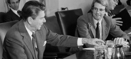 President Ronald Reagan offers youthful budget director David Stockman some jelly beans during a budget meeting in the 1980s. (photo: Bettmann/Corbis)