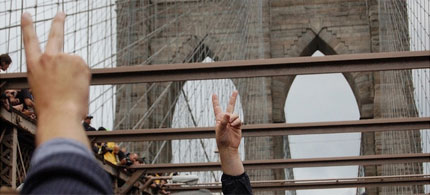 Protesters trapped on the Brooklyn Bridge by police flash peace and victory signs to comrades on the walkway above, 10/01/11. (photo: eggman/flickr)