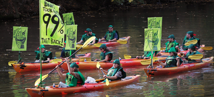 Demonstrators dressed in green Robin Hood outfits paddle their kayaks down the Chicago River, 10/10/11. (photo: Scott Olson/Getty Images)