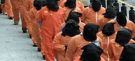 Guantanamo detainees escorted in line through prison camp. (photo: public domain)