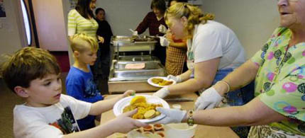 From left, Levi Gibbs, Isaiah Munk and Stephanie Gibbs are fed at a homeless facility,  12/13/11. (photo: M. Scott Moon/Peninsula Clarion)