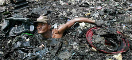 A man sifts through debris-strewn water looking for items to salvage, 04/13/11.  (photo: china.com.cn)