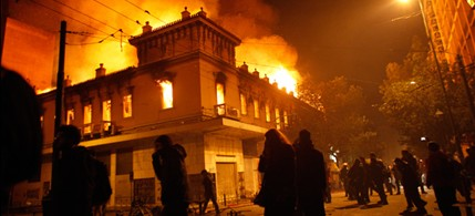 Protesters pass by a burning cinema in Athens, 02/12/12. (photo: Kostas Tsironis/AP)