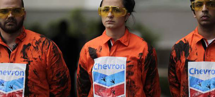 Greenpeace activists protest against an oil spill in waters off Rio de Janeiro state in front of Chevron headquarters in Rio de Janeiro, Brazil, 11/18/11. (photo: Luiza Castro/AFP/Getty Images)