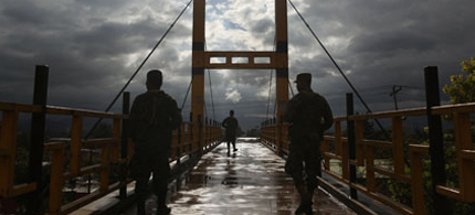 Soldiers stand guard on a bridge in Tegucigalpa, Honduras, ahead of a recent visit by US Vice President Joe Biden, 03/05/12. (photo: Esteban Felix/AP)