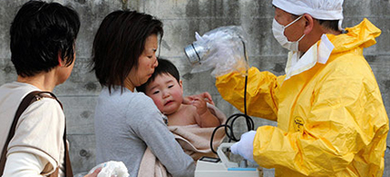 Japanese medical personnel check a mother and son for radiation exposure in Kawamata village, Fukushima prefecture, Japan. (photo: Asahi Shimbun/EPA)