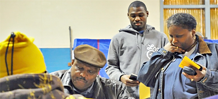 Voters hold ID as they wait to check in to vote in Primary election. (photo Matt Stanley)