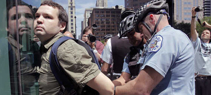 Chicago police officers take a protester into custody, as Occupy Chicago demonstrators took off into downtown streets, trying to block traffic following a march at the federal Immigration Court building, 05/15/12. (photo: Kiichiro Sato/AP)