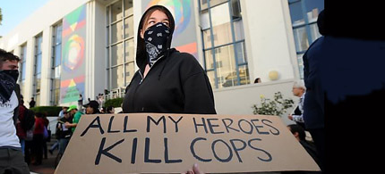 A Black Bloc protester with a sign advocating killing police. (photo: TheBlaze.com)