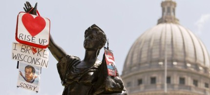 Protest signs hang from the 'Forward' statue in front of the State Capitol. (photo: Getty Images)