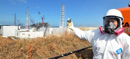 A journalist checks the radiation level with her dosimeter at the Fukushima Dai-ichi nuclear power plant in February 2012. TEPCO, the operator of Japan's crippled Fukushima nuclear plant, says it has detected record amounts of radiation in the basement of reactor number 1. (photo: AFP)