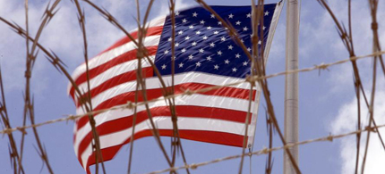An American flag behind barbedwire. (photo: Getty Images)