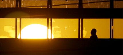 The sun rises beyond a pedestrian using a walkway between a parking garage and a medical office building March 28, 2012, in Lafayette, Ind. (photo: Michael Heinz/AP/Journal & Courier)