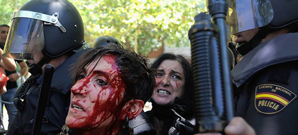A bloodied woman is detained by riot police during a demonstration by Spanish coal miners. The miners had marched to Madrid to protest government subsidy cuts for their industry. (photo: Denis Doyle/Getty Images)