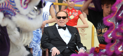 Chairman and CEO of Las Vegas Sands Corporation Sheldon Adelson, center, watches a lion dance at the opening ceremony of Sands' Cotai Central in Macau on April 11, 2012. (photo: Aaron Tam/AFP/Getty Images)