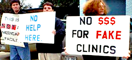 People hold signs revealing clinics lack of authenticity in front of 'Crisis Pregnancy Center.' (photo: RH Reality Check)