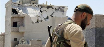 A member of the Free Syrian Army walks past a destroyed building in Azzaz, Aleppo province, July 17, 2012. (photo: Abdo/Reuters)