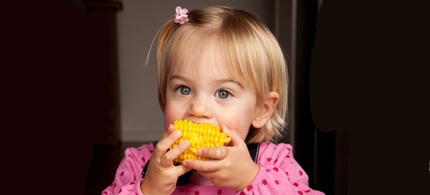 A young girl eats corn on the cob ... is it genetically modified? (photo: Shutterstock)