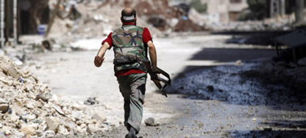 A Free Syrian Army fighter runs during clashes with the Syrian Army in the Salaheddine neighbourhood of central Aleppo, Syria, 08/07/12. (photo: Goran Tomasevic/Reuters)