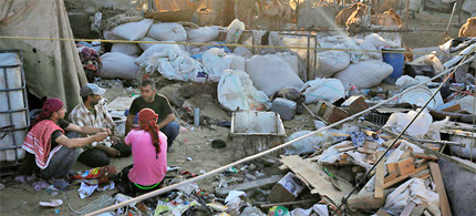 Palestinians in a makeshift, rubble-strewn home in Gaza's Forgotten Neighborhood, an extreme example of Gaza's poverty. (photo: Ed Ou/NYT)