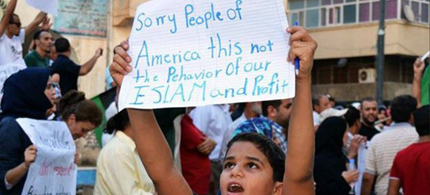 Young Egyptian holds sign apologizing for the Benghazi attack. (photo: Reuters)