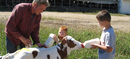 Jack and Garrett help their dad feed calves. (photo: Dairy Mom)