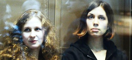 Pussy Riot band members Maria Alyokhina (left) and Nadezhda Tolokonnikova sit in a glass cage during their court hearing. (photo: Natalia Kolesnikova/AFP/Getty Images)