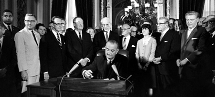 In this Aug. 6, 1965 photo, President Lyndon Baines Johnson signs the Voting Rights Act of 1965 in a ceremony in the President's Room near the Senate Chambers on Capitol Hill in Washington. (photo: AP)