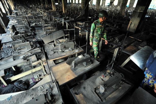A Bangladeshi Army personnel walks through the rows of burnt sewing machines in the Tazreen factory, which caught fire Sunday, killing more than 110 workers. (Stringer/AFP/Getty Images)