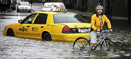 A cyclist makes his way past a stranded taxi on a flooded New York City street as Tropical Storm Irene passes through the city. (photo: Peter Morgan/AP)