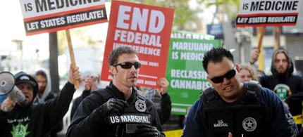 With marijuana proponents chanting behind them, U.S. marshals raid Oaksterdam University in Oakland, Calif., on Monday, April 2, 2012. With voters around the country voting for legalization, President Obama is left to choose between enforcing federal laws or looking the other way. (photo: Noah Berger/AP)