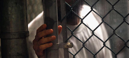 A detainee stands at a fence inside the detention center in September 2010 in Guantanamo Bay, Cuba. (photo: John Moore/Getty Images)