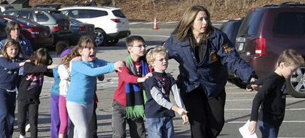 Connecticut State Police lead children from the Sandy Hook Elementary School in Newtown, Conn., following a shooting there Friday, Dec. 14, 2012. (photo: Shannon Hicks/Newtown Bee)