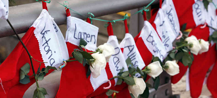 Christmas stockings with the names of shooting victims hang from a railing in the Sandy Hook village of Newtown, Conn. (photo: Julio Cortez/AP)