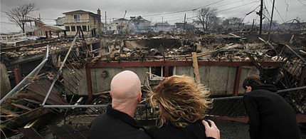 Robert and Laura Connolly survey the damage of Sandy. (photo: Mark Lennihan/AP)
