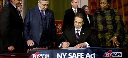 New York Gov. Andrew Cuomo and legislative leaders at the signing of the state's new weapons law on Tuesday afternoon. (photo: AP)