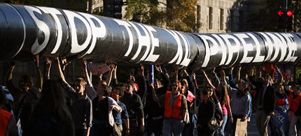 A mock oil pipeline is carried during a Keystone XL tar sands oil pipeline demonstration near the White House in Washington. (photo: Andrew Harrer/Bloomberg)