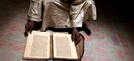 Abdoulaye Cissé of the Ahmed Baba Institute with a manuscript that was hidden from extremists, who set fire to others. (photo: Tyler Hicks/The New York Times)