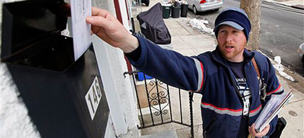 Letter carrier Kevin Pownall delivers mail in Philadelphia. (photo: Matt Rourke/AP)