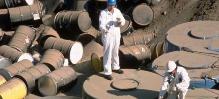 Barrels of low-level Class A commercial nuclear waste are checked with a Geiger counter in a trench at the Hanford Nuclear Reservation in Washington state, 10/18/88. (photo: Roger Ressmeyer/Corbis)