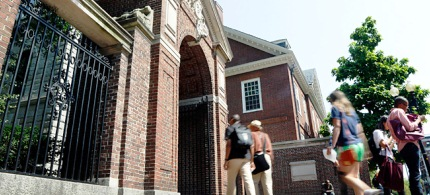 Pedestrians walk through a gate on the campus of Harvard University in Cambridge, Mass. (photo: AP/Elise Amendola)