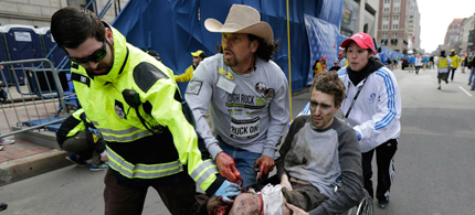 Carlos Arredondo (wearing cowboy hat) helps an injured man past the finish line of the 2013 Boston Marathon. Arredondo who lit himself on fire after learning that his son was killed in Iraq in 2004, had already completed the Boston Marathon when two explosions inspired him to come to the aid of others. (photo: Charles Krupa/AP)
