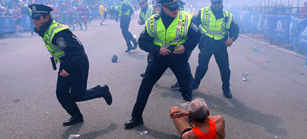 Boston Police stand over downed runner seconds after explosions. (photo: John Tlumacki/The Boston Globe)