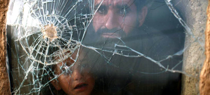 Afghan father and son look out a window with a bullet hole. (photo: Reuters)